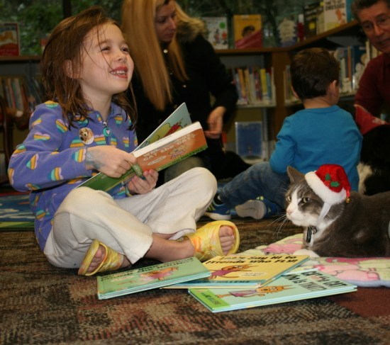 Shannon Scully, 5, reads to Smokey during the Mountlake Terrace's Reading with Rover program Saturday morning. Children read aloud to specially trained service dogs and a cat during the event. (Photos by David Pan)