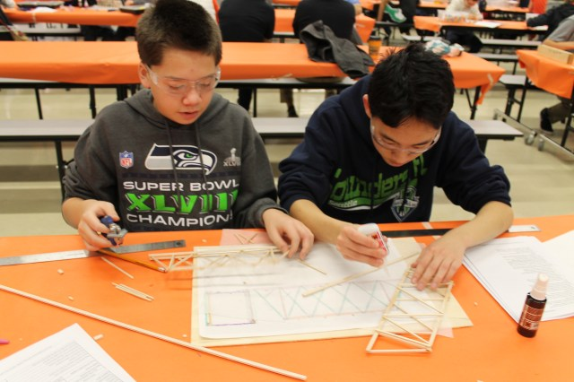 BTMS students Trevor Doan (left) and Daniel Quach work on their entry in the Structural Challenge at the Jan. 10 Technology Student Association regional competition held at Brier Terrace Middle School. (Photo by Marianne Nacanaynay)