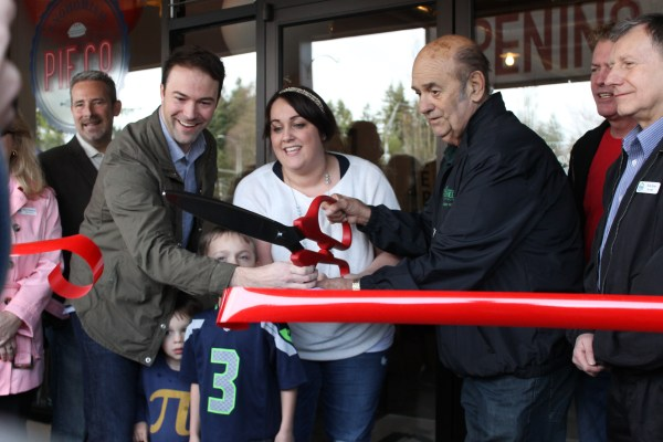 : Ryan and Jenny Brien (left and center) and Mountlake Terrace Mayor Jerry Smith (right) cut the ribbon during the grand opening ceremony of the Snohomish Pie Company Mountlake Terrace location on Saturday. Jenny Brien owns the bakery and its parent outlet in Snohomish.
