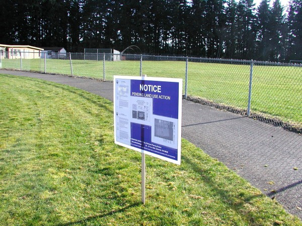 A sign alerting passersby to the changes planned for the playfields at Old Woodway High School. Edmonds Heights K-12 classrooms are located at the left in the photo. The Edmonds School District plans to replace the grass baseball field directly above the sign with two turf fields later this spring.