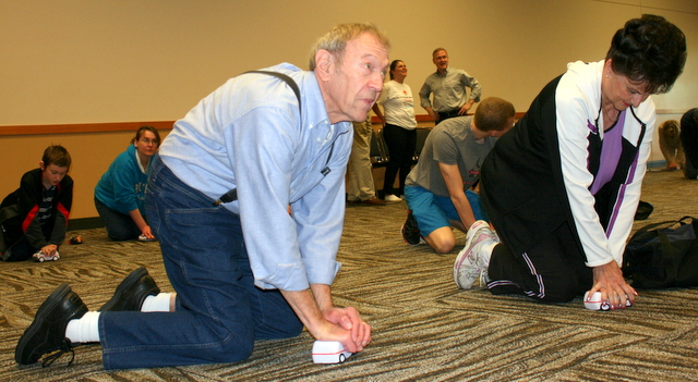 Mel Reece and his wife Helen (right) practice hands-only CPR on a toy truck during during Save-a-Life Saturday at the Lynnwood Convention Center (Photos by David Pan)