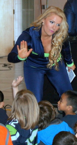 Seattle Seahawks cheerleader Tamaria Favell high fives a student.