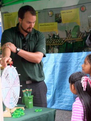 Waste Management Recycling Education intern Brian Peake (left) plays spin the wheel with two girls.