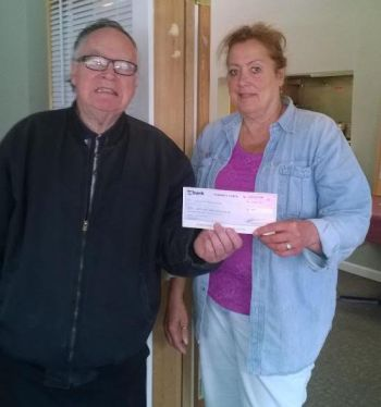Al Rutledge, organizer of the Edmonds Car Show on Highway 99, presents $161 check to Cynthia Wesley, president of the Mountlake Terrace Senior Center Board of Directors. The money will go toward purchasing a new van for the senior center.