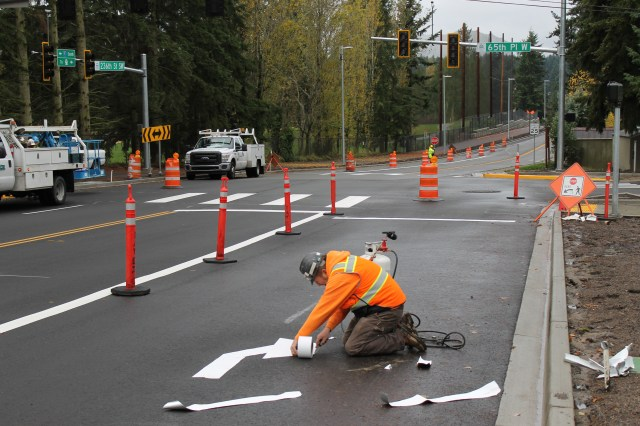 A crew member applies the turn arrow for the new right-turn only lane of westbound 236th Street SW at 65th Place West, a part of the redesigned Mountlake Terrace intersection just west of I-5.