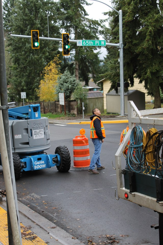 A worker checks on the new signals at the 236th Street SW/65th Place W intersection shortly after they were turned on for the first time around 10:00 a.m. on Monday.