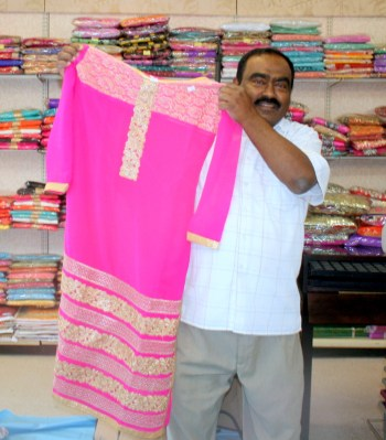 In addition to offering a wide variety of groceries, Paradise Market also sells Indian Clothing. Owner Mohammed Yusuf displays a dress. (Photo by David Pan)