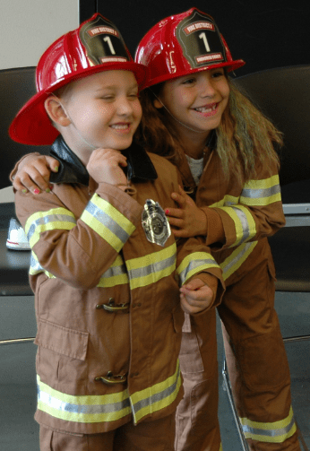 Two young firefighters model firefighting gear.