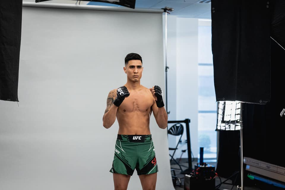 Luis Saldana poses with his fists up for a UFC photoshoot. He is wearing UFC gloves and green Venum shorts.