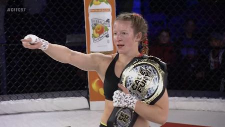 Elise Reed poins to outside the CFFC cage while holding a championship around her shoulder.