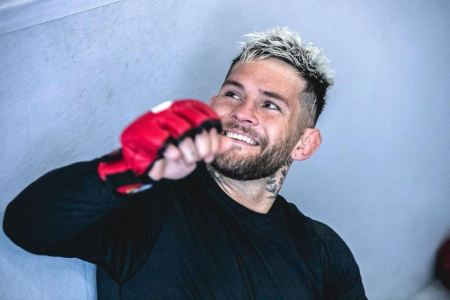 Vince Murdock smiles while wearing MMA gloves.