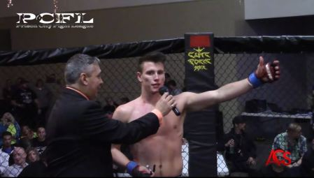 Collin Anglin stretches his arm out while speaking to an interviewer inside an MMA cage.
