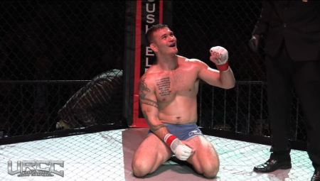 Orion Cosce raises his fist to celebrate with an out-of-frame bystander while seated in an MMA cage.