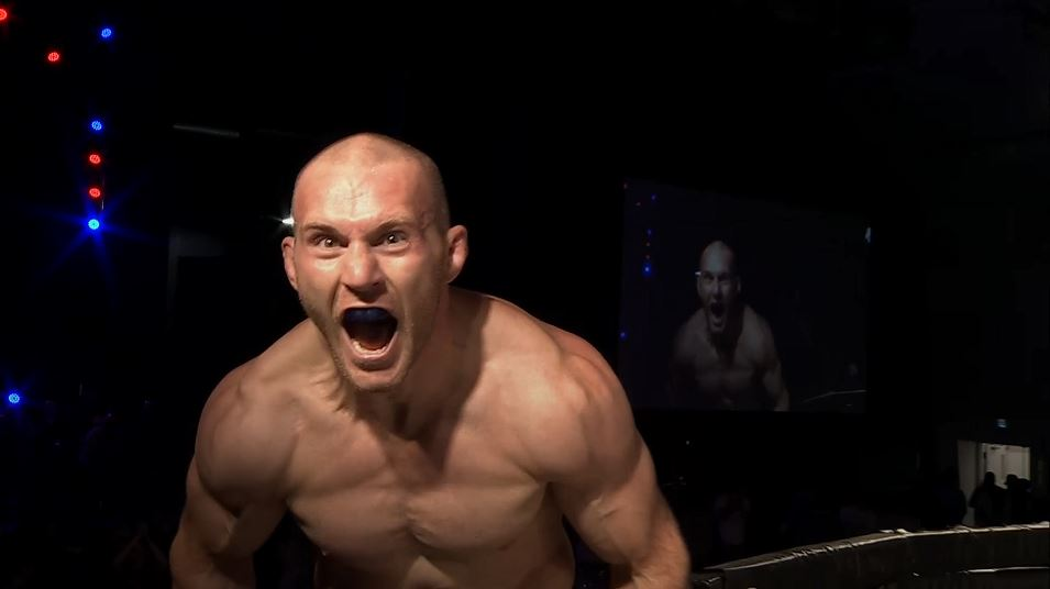 Graham Park shouts while sitting atop an MMA cage.