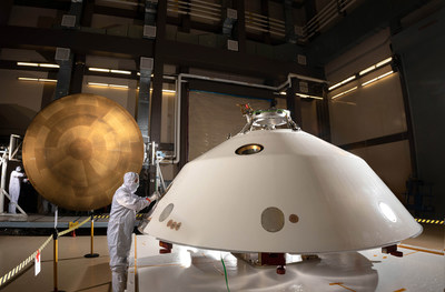 Lockheed Martin engineers work on the construction of the aeroshell for the Mars 2020 mission. The cone-shaped back shell and orange heat shield will protect the Perseverance rover on its way to the surface of Mars.