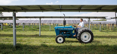 Byron Kominek, owner of Jack's Solar Garden, riding his family's tractor through their solar power system. Photo courtesy of Werner Slocum, National Renewable Energy Laboratory