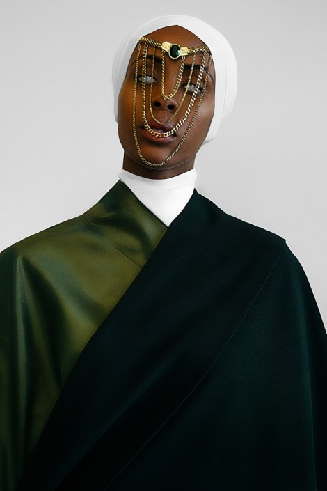 Portrait of an African-American man in a dark green and black robe with white collar and turban. A series of several chains drape across his face, hanging from his turban across his forehead and nose.