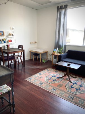 Spacious counselling office with window, area for doing art, sand table and access to play therapy tools