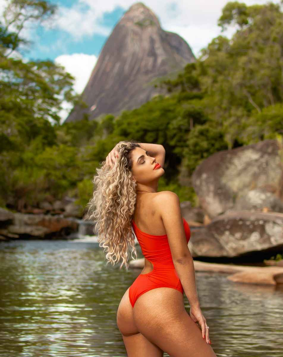 seductive dreamy model in red swimwear near river in mountains