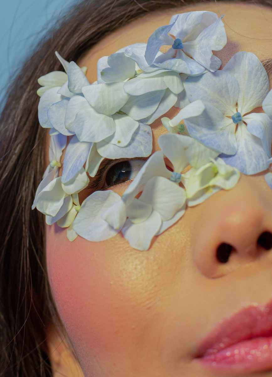 crop asian woman with blue petals on face