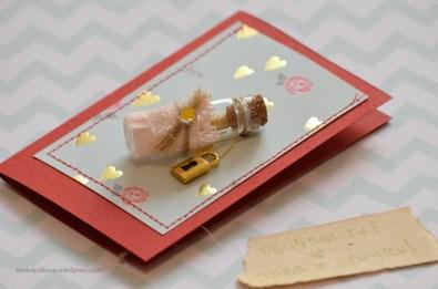 пергамент навит на руло и поставен в малка бутилка, декорирана със златен катинар <3