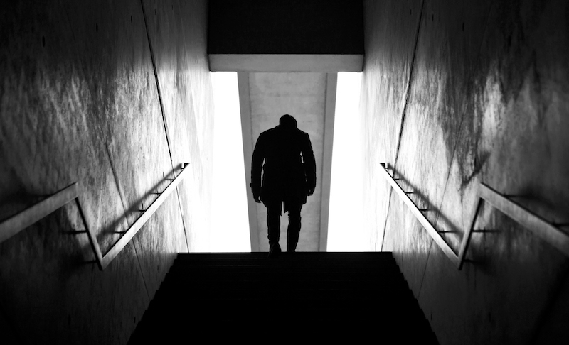 Black and White Photo of Dax J from behind walking up a set of stairs