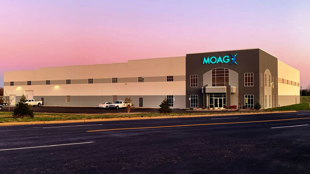 Clear morning pastel sky behind the new Moag Glass manufacturing building, few white trucks in the lot and a foreground of four lane asphalt