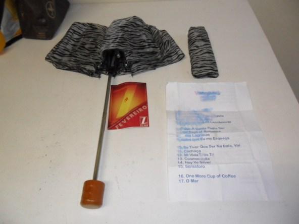 Na foto: Sombrinha guerreira, Setlist manchada de cerveja e um flyer que ganhei no bar do banheiro sem tranca.