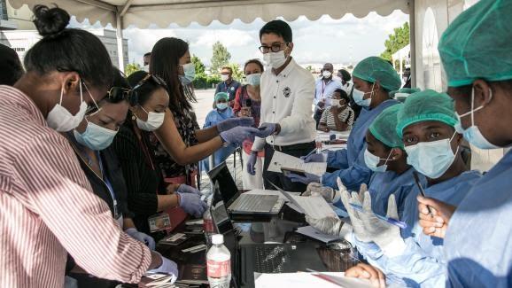 Le président malgache (au centre avec masque et lunettes de vue) dans un centre de tests de dépistage du Covid-19 à Antananarivo le 31 mars 2020.