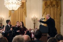 A White House staff member reaches for the microphone held by CNN's Jim Acosta as he questions Donald Trump.