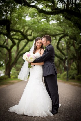 A bride and groom embrace under the Avenue of the Oaks