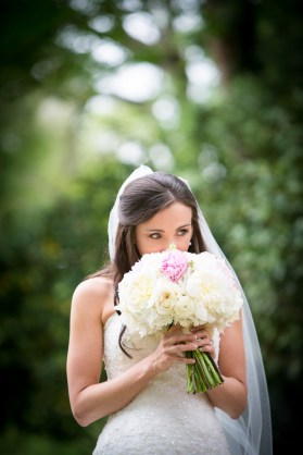 A bride smells the aroma of a bouquet of peonies and ranunculus
