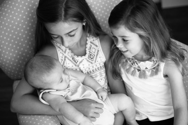 Big sisters hold their baby brother