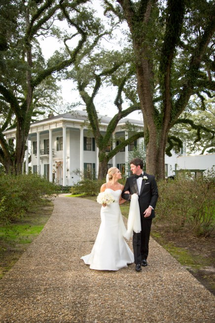 A bride and groom walk a driveway at the Bragg-Mitchell Mansion