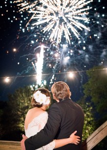 Bride and groom watch fireworks burst