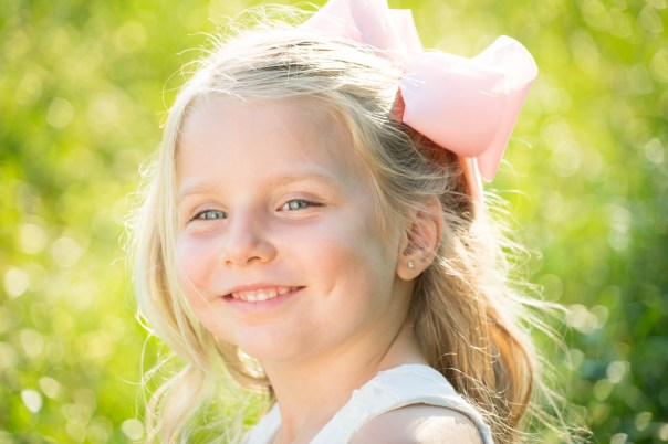 Smiling little girl with pink bow