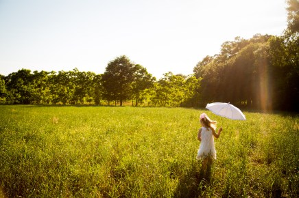 Little girl with white parasol in a field of grass