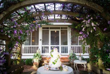 A wedding cake under an arbor of wisteria