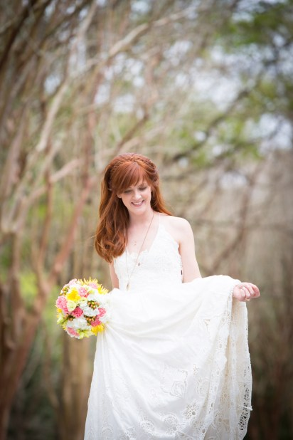 A red-headed bride walks down a path