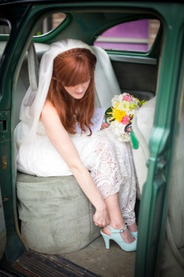 A bride puts on her heels in a vintage car