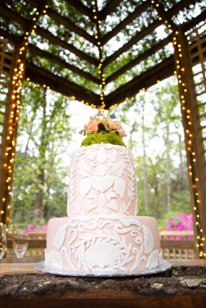 A two-tier pink cake under lights