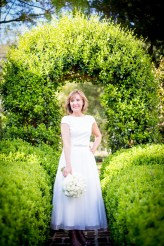Chic bride under an arbor of greenery