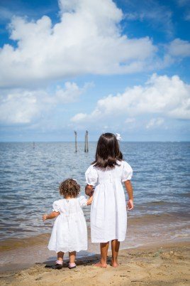 Sisters in white on a Fairhope, Alabama, beach.