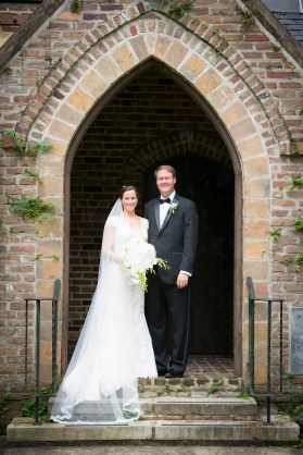 Traditional wedding portrait of a bride and groom under an arch