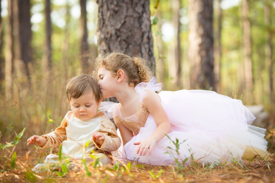 A little girl kisses her baby brother on a bed of pine straw