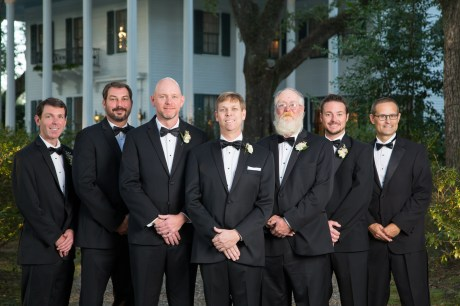 The groomsmen and the groom in classic, black tuxedos