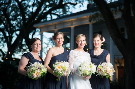 The bride and her bridesmaids in full-length navy gowns