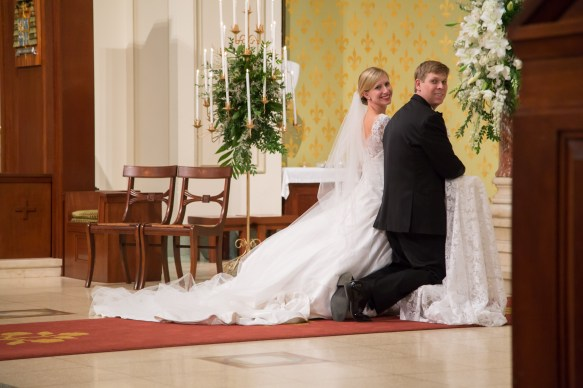 Bride and groom kneeling at the altar of the Cathedral of the Immaculate Conception