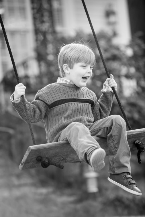 A little boy swings in the front yard of his Old Dauphin Way Historic District home