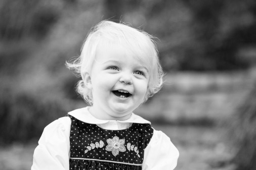 Blonde toddler laughs at her parents' silly faces